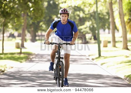 Man Cycling Through Park