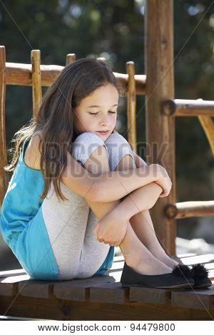 Sad Young Girl Sitting On Climbing Frame