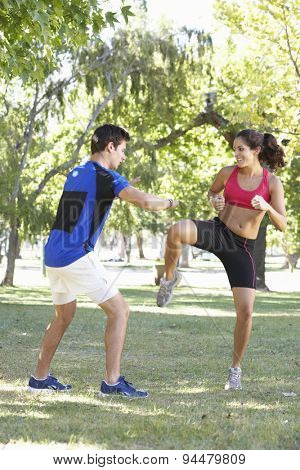 Young Woman Working With Personal Trainer In Park