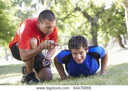 Young Man Working With Personal Trainer In Park