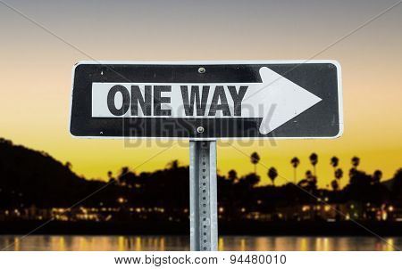 One Way direction sign with sunset background
