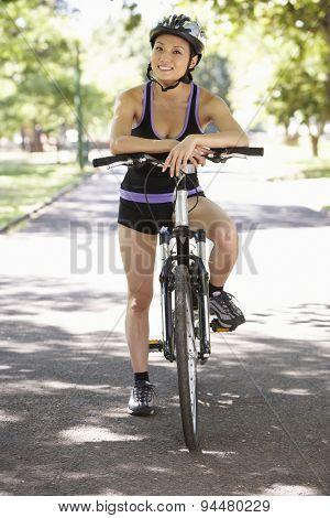 Woman Cycling Through Park