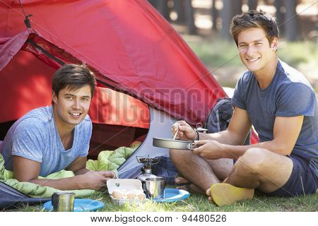 Two Young Men Cooking On Camping Stove Outside Tent