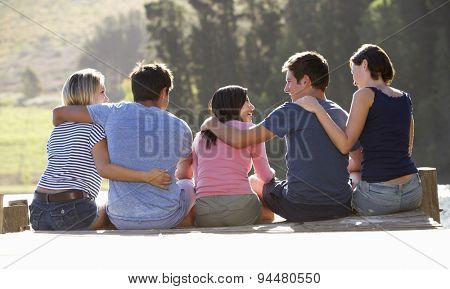 Group Of Young Friends Sitting On Wooden Jetty Looking Out Over Lake