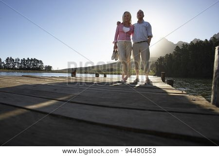 Senior Couple Standing On Wooden Jetty Looking Out Over Lake