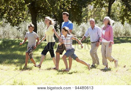 Three Generation Family Walking In Countryside