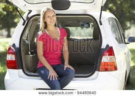 Young Woman Sitting In Trunk Of Car