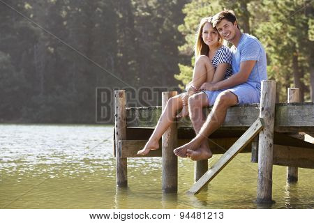 Young Romantic Couple Sitting On Wooden Jetty Looking Out Over Lake