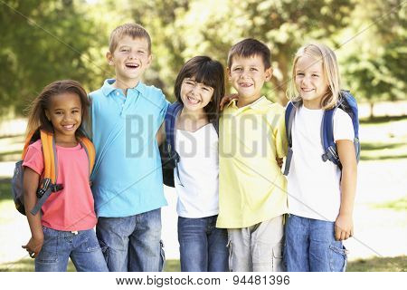Group Of Primary School Pupils Wearing Backpacks In Park