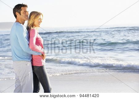 Young Couple Standing On Sandy Beach Looking Out To Sea