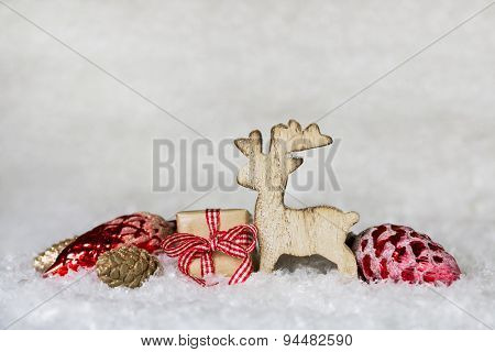 Classical christmas decoration with snow and wooden moose with red gifts and balls.
