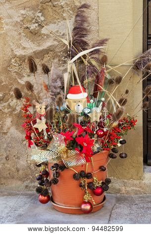 Outdoor christmas decoration with a teddy santa and dry plants.