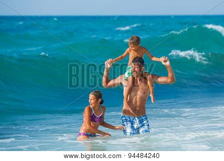 Father and children playing in the sea
