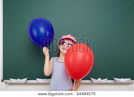 Schoolgirl with balloon near the school board