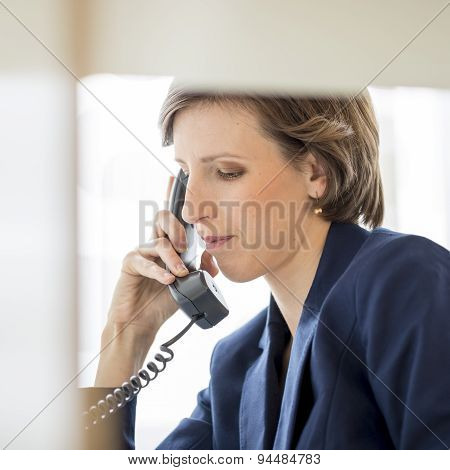 Successful Young Businesswoman Sitting At Her Desk Making A Phone Call