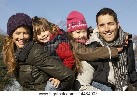 Parents giving piggybacks to children on winter walk