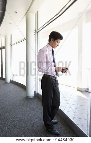 Young Businesman Standing In Corridor Of Modern Office Building Using Mobile Phone