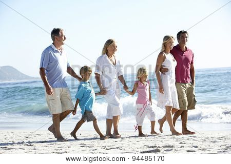 Three Generation Family Walking Along Sandy Beach