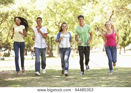 Group Of Teenage Friends Running In Park