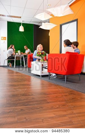 Modern styled, colorful business lounge, with several project teams sitting at tables during informal meetings