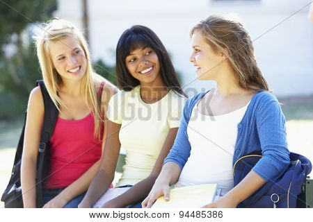 Three Female College Students Sitting On Bench With Textbooks