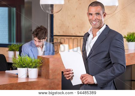 Handsome businessman with documents in front of the reception
