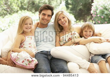 Portrait Of Young Family Relaxing On Sofa