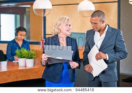 Two colleagues meeting in front of a reception desk where a secretary answers calls to discuss project notes