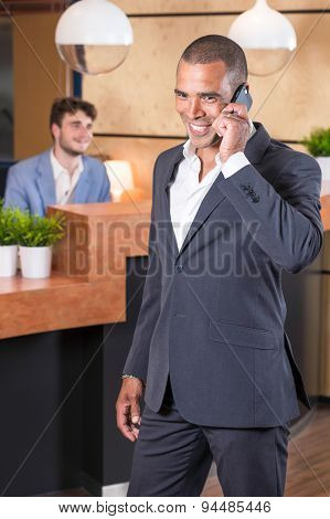 Businessman on the phone in the lobby of his office