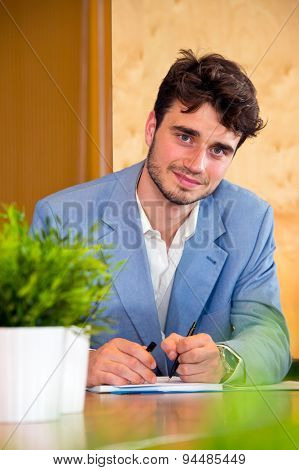 Young, eager apprentice, taking notes and learning on the job, wearing a blue jacket, looking kindly into the camera