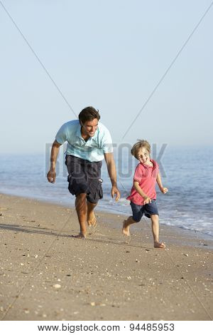 Father And Son Running Along Beach