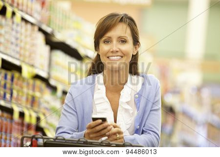 Woman using cellphone in supermarket