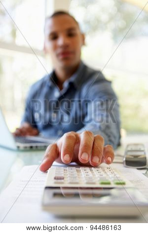 Young Man On Using Calculator At Home