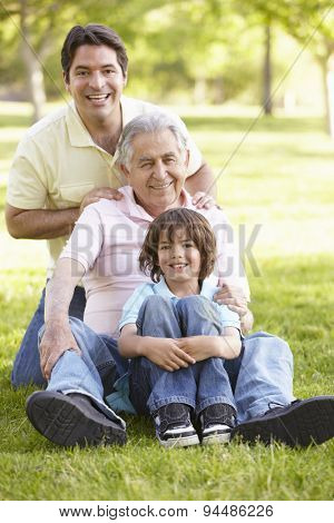 Hispanic Grandfather, Father And Son Relaxing In Park