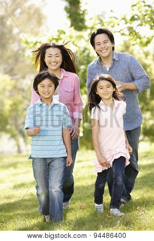 Asian family running in park