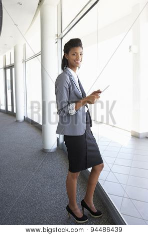 Young Businesswoman Standing In Corridor Of Modern Office Building Using Tablet Computer