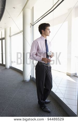 Young Businessman Standing In Corridor Of Modern Office Building Drinking Coffee