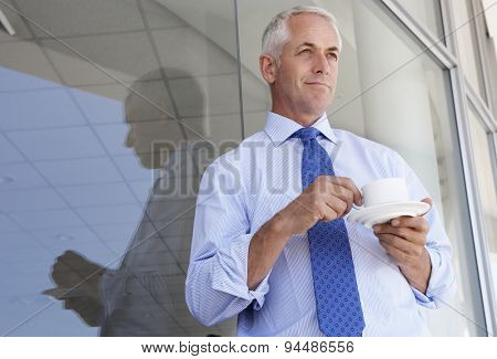 Mature Businessman Standing Outside Modern Office Drinking Coffee