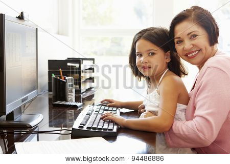 Senior Hispanic woman with computer and grandchild