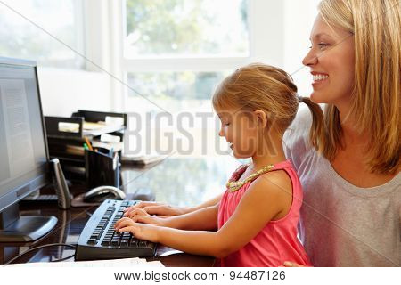 Mother working in home office with daughter