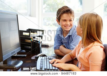 Young boy and girl using computer at home