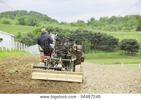 The back of an Amish man cultivating his hilltop field in the springtime with a cultivator and a pair of horses.