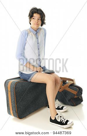 An attractive young teen looking for her traveling companion as she sits on her suitcase, her passport and boarding pass in her lap.  On a white background.