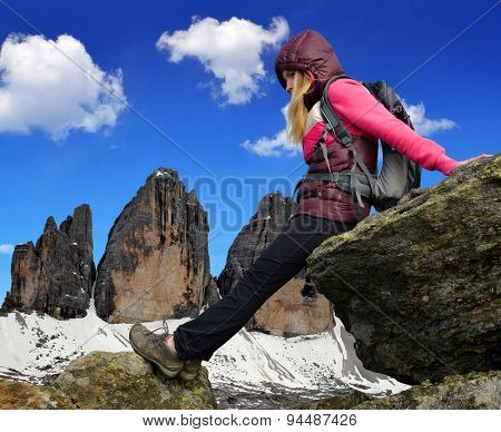 Girl on rock, in the background Tre Cime di Lavaredo - Dolomites, Italy