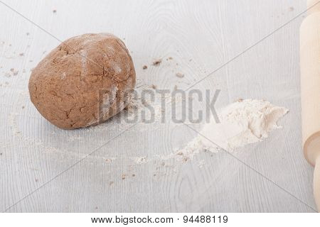 Dough with rolling pin on wooden table.