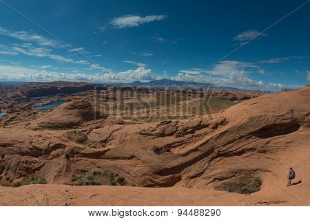 Girl Hiker Walking Down Wavy Sandstone Towards The Lake Powell
