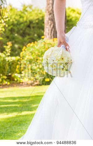 Detail Of Bride Holds In Hand A Wedding Bouquet Of Flowers In A Garden