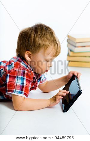 Boy Lying On The Floor With Tablet Computer