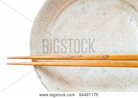 Brown wood chopsticks and white ceramic on white background
