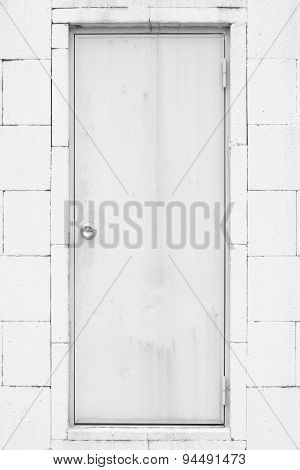 White metal door and concrete block wall background